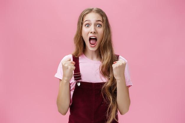 コーデュロイのオーバーオールを着たスリムで面白くてかわいい若い女の子が拳を握りしめ、お気に入りのチームの突然の勝利に驚いた驚きと喜びから叫んで勝利を収めた屋内ショット。