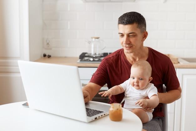 バーガンディのtシャツを着て、白いキッチンでポーズをとって、赤ちゃんを手にノートパソコンの前に座って、ノートに入力して、笑顔のハンサムなフリーランサーの男性の屋内ショット。