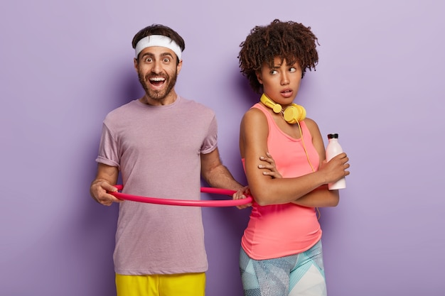 웃는 남자의 실내 샷은 보라색 티셔츠를 입은 훌라 후프를 회전시키고, 좋은 신체 모양을 유지하고, 아프리카 여자는 뒤로 서서, 보라색 벽 위에 고립 된 신선한 물 한 병을 보유하고 있습니다. 건강한 생활