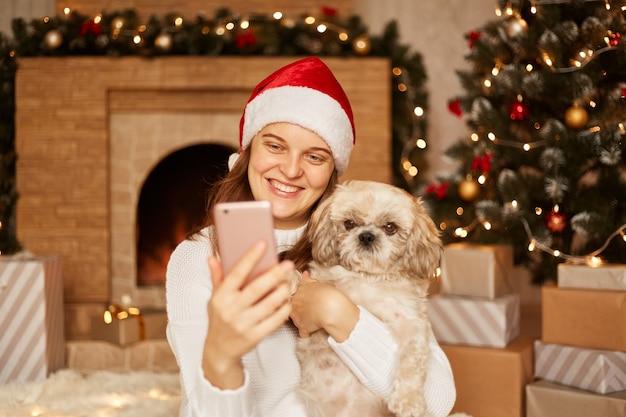 흰색 스웨터와 산타클로스 모자를 쓴 웃는 여성이 북경 개를 안고 화상 통화를 하거나 라이브 스트리밍을 하고 가제트 화면을 보고 행복을 표현하는 실내 사진.