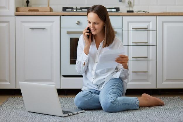 笑顔の若いヨーロッパの女性の服を着た白いシャツとジーンズが紙のシートを持ってキッチンに座ってスマートフォンで話し、ノートパソコンのディスプレイを見て笑顔の屋内ショット。