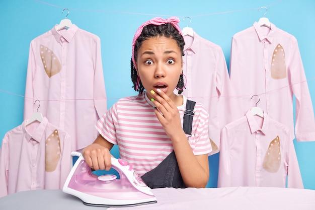 驚いた若いアフリカ系アメリカ人の主婦がカメラに驚いて見つめる屋内ショットは、アイロン台の近くの不思議なスタンドから息を止めます家事をしている忙しい洗濯室で服のポーズをアイロンをかけます