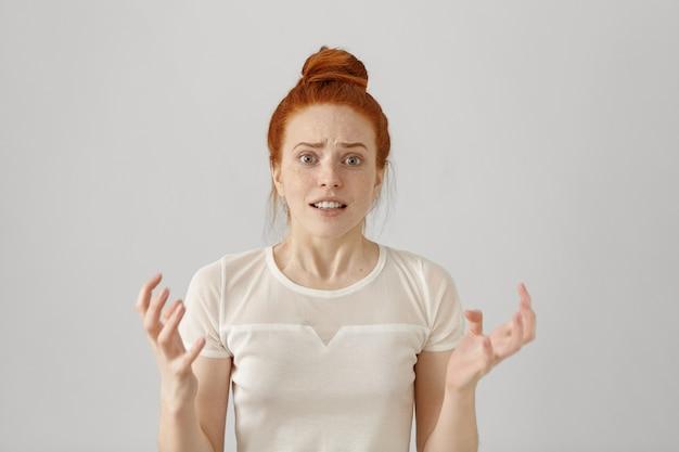 Снимок напряженной и раздраженной молодой рыжей кавказской женщины в помещении