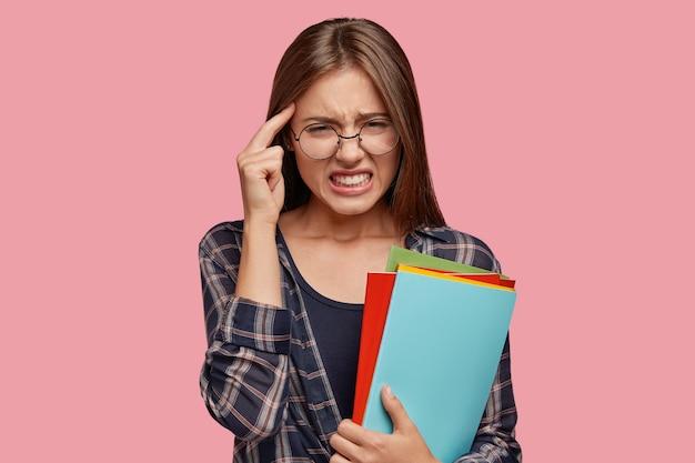 ストレスの多いヨーロッパの女性の屋内ショットは、こめかみに手を保ち、頭痛に苦しみ、歯を食いしばる