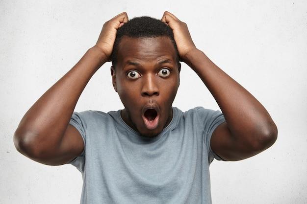 驚いた表情の若いアフリカ系アメリカ人の学生または顧客を驚かせた驚いた表情の屋内ショット。買い物中に大きなセール価格にショックを受け、驚いた表情で手をつないでいます。