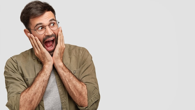 馬鹿げた驚いた白人男性の屋内ショットは、暗い無精ひげを持っており、顎を落とし続け、両手のひらで頬に触れ、何かに反応します