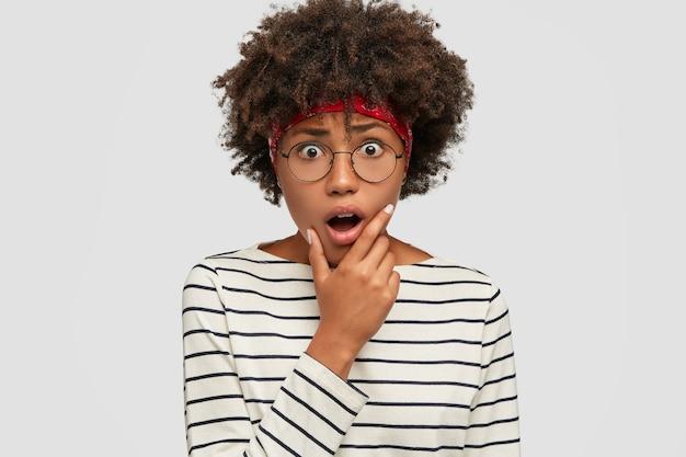 愚かな黒人女性の屋内ショットは、顎を落とし続け、恐怖に見え、カジュアルな服を着ています