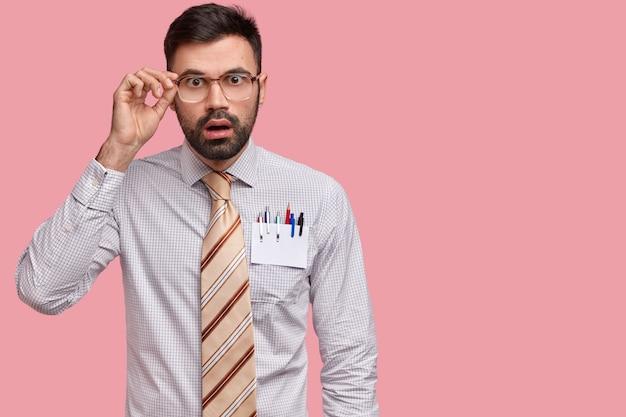 愚かな無精ひげを生やした男性の建築家の屋内ショットは、眼鏡のフレームに手を保ち、衝撃的なニュースを聞きます