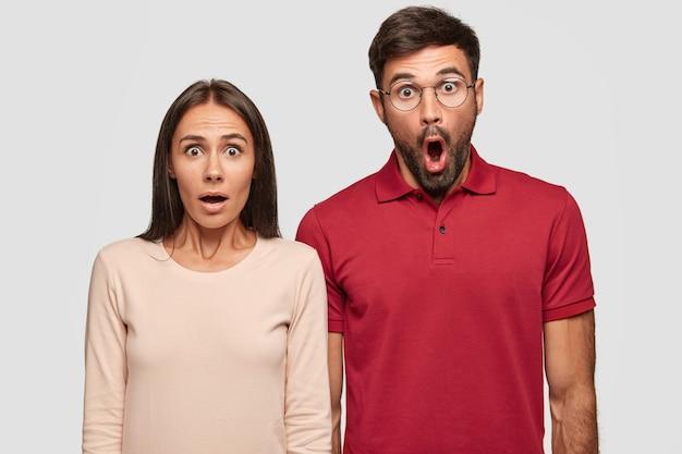 Снимок в помещении ошеломленных молодой европейской женщины и мужчины с удивленными выражениями лиц, с открытыми ртами