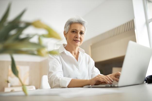 개방형 일반 휴대용 컴퓨터 앞에 책상에 앉아 세련된 경험이 풍부한 여성 마케팅 전문가의 실내 촬영