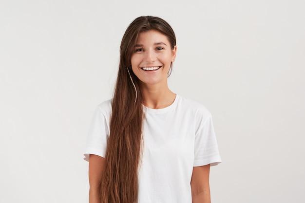 Стильная молодая женщина в помещении, укладывает свои растрепанные темные волосы в сторону, широко улыбается, чувствует себя счастливой. носит повседневную белую футболку