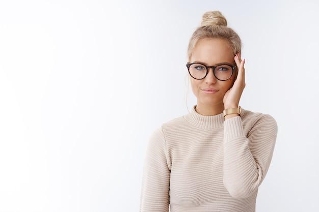 Снимок в помещении успешной дерзкой и стильной европейской блондинки с причесанной стрижкой в очках, высокомерно ухмыляющейся и самоуверенно проверяющей волосы, выглядящей профессионально в камеру над белой стеной