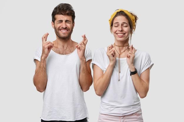 미신적 인 백인 젊은 여자와 남자의 실내 촬영은 손가락을 교차하고, 희망을 가지고, 즐거운 것을 꿈꾸며, 서로 옆에 서고, 눈을 감고, 넓게 웃으며, 행운을 믿습니다.