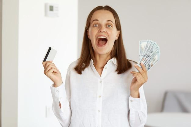 Снимок удивленной женщины в белой рубашке повседневного стиля в помещении, которая позирует в светлой комнате дома, радостно кричит, держит в руках долларовые банкноты и кредитную карту, выигрывает в лотерею.