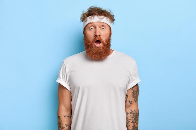 赤い髪の驚いたあごひげを生やした男の屋内ショットは、驚きで見つめ、毎日体操をしています