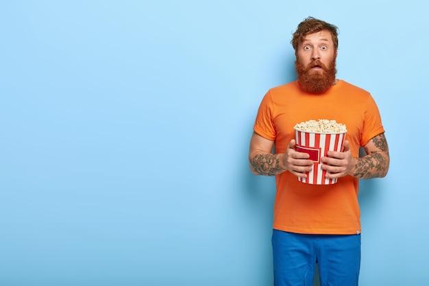 驚いたひげを生やした赤毛の男の屋内ショットはポップコーンを食べる