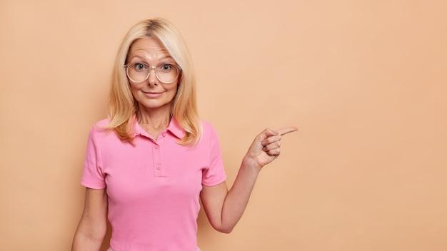놀란 금발의 유럽 여성이 빈 공간을 가리키는 실내 사진은 베이지색 벽에 격리된 투명한 안경과 분홍색 티셔츠를 입은 특별 제안을 제시합니다.