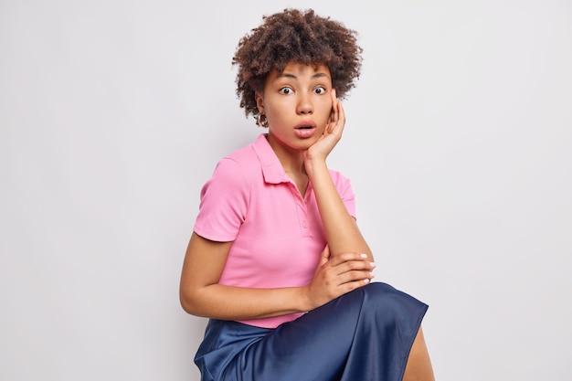 驚いた巻き毛のアフロアメリカ人女性の屋内ショットはピンクのtシャツを着ており、青いスカートは頬に手を保ち、白い壁に一人で座っている衝撃的なものに反応します