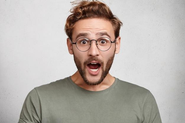 Снимок удивленного европейца в помещении, шокированного широко раскрывающим рот