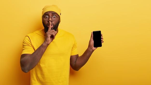 Крытый снимок удивленного красивого парня в очках, позирующего со своим телефоном