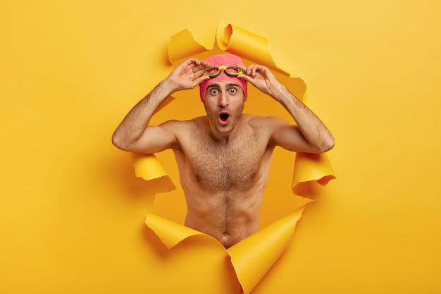 Снимок удивленного счастливого пловца в помещении, держащего руки в очках, позирует без рубашки
