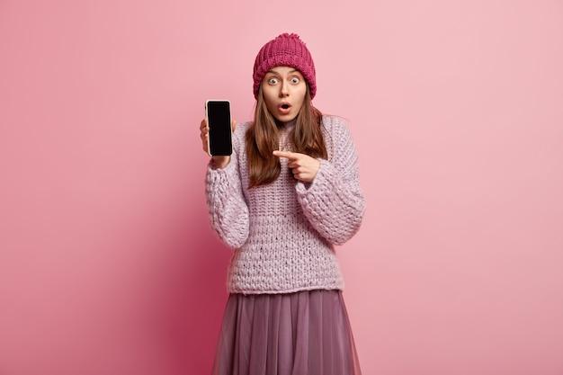 Снимок удивленной миллениальной девушки в помещении показывает дисплей смартфона и рекламирует красивое приложение для редактирования фотографий