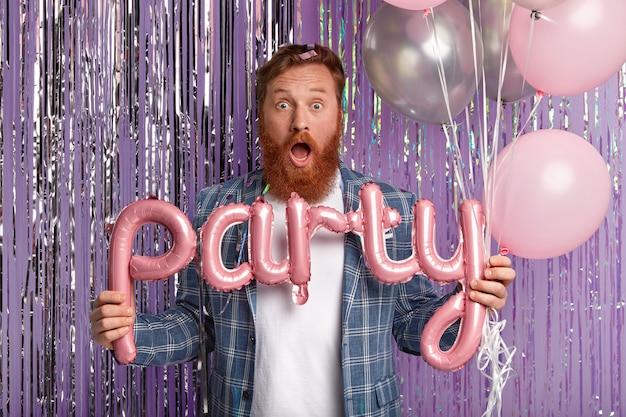 놀란 빨간 머리 남자의 실내 촬영은 놀라움에서 입을 열고, 편지 모양의 풍선을 보유하고, 밝은 반짝이로 보라색 벽 위에 고립 된 유행의 옷을 입고 있습니다. 파티 시간 개념