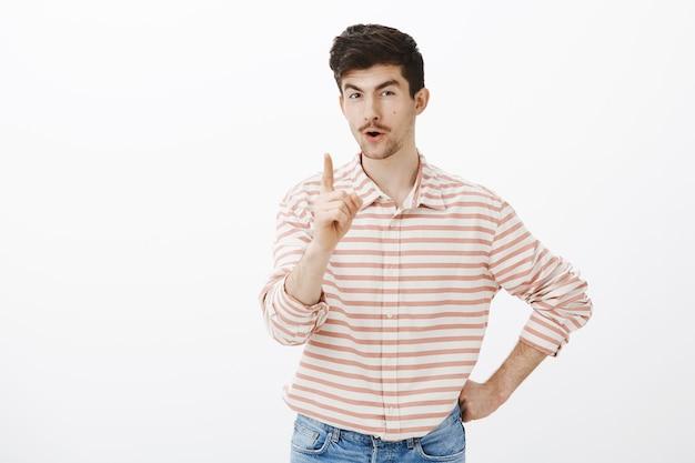 В помещении: подозрительный игривый европейский парень со смешным выражением лица, поднимающий руку и трясущий указательным пальцем, угрожающий или высказывающий собственное мнение, учит брата, как вести себя за серой стеной