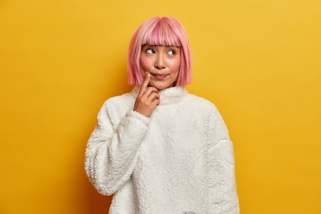 В помещении: подозрительная задумчивая женщина с восточной внешностью, делает предположения, о чем-то думает, держит палец у рта, одетая в белый джемпер.