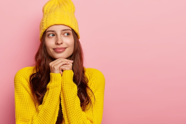 В помещении: нежная задумчивая женщина держит руки вместе под подбородком, носит стильную желтую шляпу и теплый свитер, позирует у розовой стены, пустое пространство.