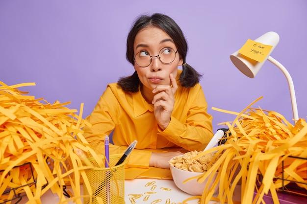 Задумчивая азиатская женщина в помещении, задумчивая, смотрит в сторону, задумчиво думает о завершении нового творческого задания, в окружении груды вырезанной желтой бумаги сидит в пространстве для коворкинга, изолированном над фиолетовой стеной студии.