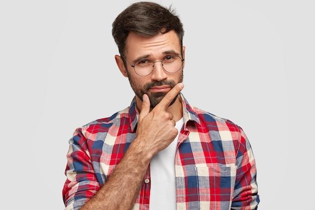 思いやりのあるひげを生やした若いヨーロッパ人の男性の屋内ショットは、あごの下に手を保ち、真剣に見え、カジュアルな市松模様のシャツを着て、白い壁に隔離されています。男らしさの概念。