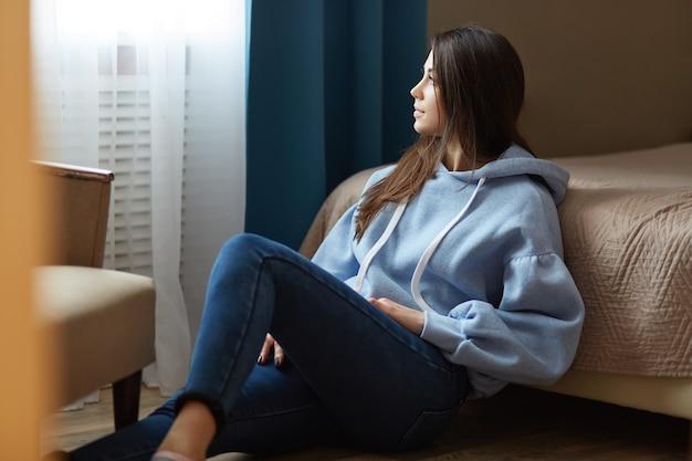 Внутренний снимок задумчивой темноволосой женщины, одетой в синюю толстовку