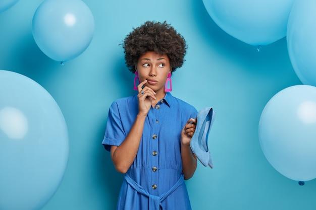 ハイヒール中毒の思慮深い暗い肌の女性の屋内ショット、ドレスに合う美しいエレガントな青い靴、特別な機会のためのドレスを保持し、買い物に行った後に喜びを得て、目をそらします