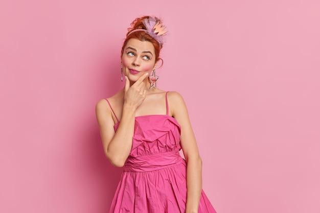 思いやりのある夢のような赤毛の女性の屋内ショットは、あごが化粧をしています