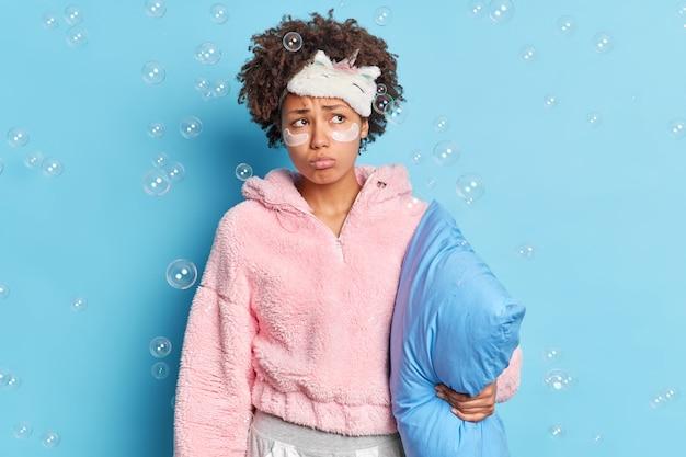 寝間着で思慮深い不幸なアフリカ系アメリカ人女性の屋内ショットは枕を保持します