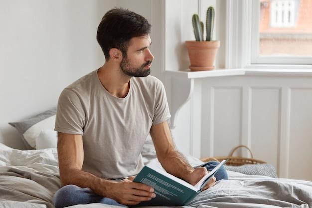 사려 깊은 형태가 이루어지지 않은 남자의 실내 촬영은 책을 읽고, 성공적인 프로젝트를위한 몇 가지 팁을 배우고, 침대에 앉고, 캐주얼 한 옷을 입고, 옆으로 집중하고, 어두운 수염을 가지고 있습니다. 여가와 문학 개념