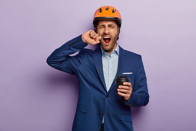 オフィスで上品なスーツと赤いヘルメットでポーズをとって疲れた過労ビジネスマンの屋内ショット