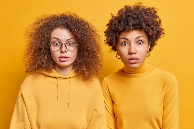 Снимок в помещении: две подруги смешанной расы с вьющимися волосами смотрят очень удивленно, изумленно вздыхают, не могут поверить, что их глаза стоят близко друг к другу у желтой стены. omg концепция