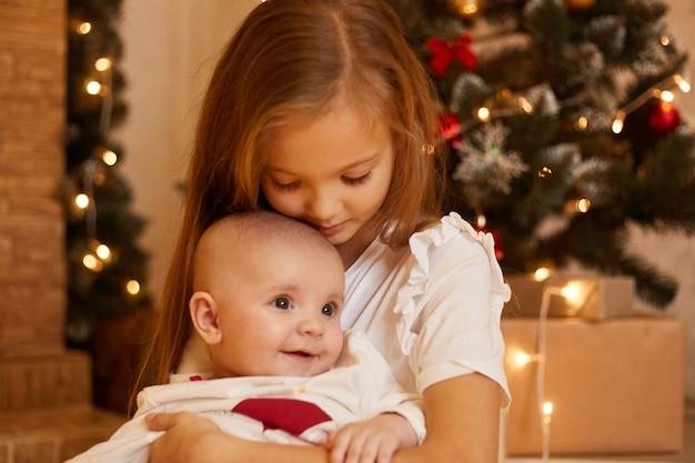 自宅のクリスマスツリーの近くでポーズをとっている2人の姉妹、愛を込めて幼児の赤ちゃんを抱き締める長女、メリークリスマスと新年あけましておめでとうございます、お祭りの部屋の子供たちの屋内ショット。