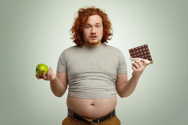 그는 한 손에 신선한 유기농 사과와 다른 초콜릿의 맛있는 바 사이에서 선택해야하기 때문에 어려운 선택에 직면 불확실한 혼란 통통 젊은 남성의 실내 샷. 딜레마, 다이어트 및 음식