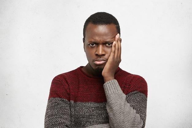 暖かいセーターを着ている不幸な若いアフリカ人の屋内撮影
