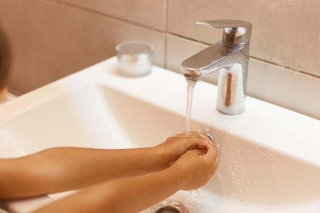 화장실에서 알 수 없는 아이의 손 씻기, 물 속에서 손 잡고, 위생적인 정화 절차, 미생물이 몸에 들어가는 것을 방지하기 위해 손을 씻는 실내 사진.
