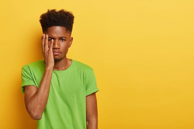 Снимок в помещении: расстроенный темнокожий мужчина со стрижкой афро, закрывает лицо ладонью, с усталым выражением лица, много работает, готовясь к экзамену, у него дедлайн, в зеленой футболке