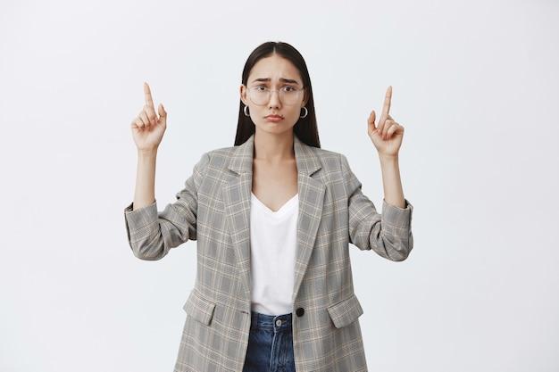 Снимок в помещении: расстроенная и недовольная привлекательная женщина в очках и куртке поверх футболки, дутая и хмурящаяся от печали, указывая вверх