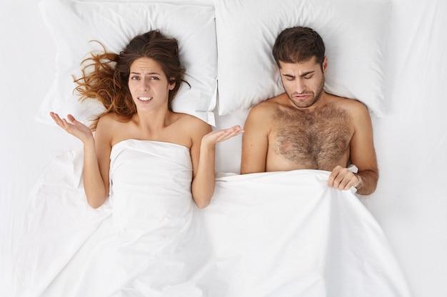 Снимок в помещении: расстроенная женщина в постели в замешательстве пожимает плечами и переживает за своего мужа, страдающего импотенцией.