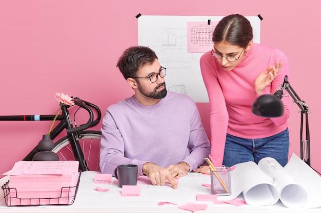 女性と男性のパートナーの屋内ショットは、デスクトップでポーズをとる青写真と建築スケッチについてのプロジェクトトークで生産性ブレインストーミングのアイデアについて話し合います。チームワークコラボレーション協力コンセプト