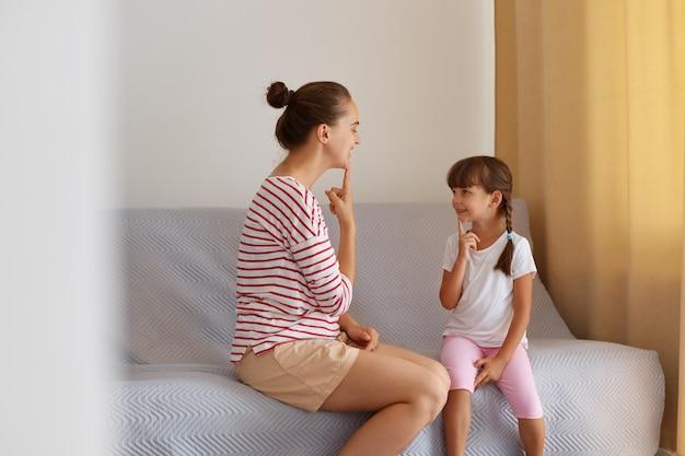 어린 소녀와 함께 소파에 앉아 머리를 금지한 여성의 실내 사진, 어린이에게 소리를 발음하는 방법, 전문 언어 병리학자와의 개인 레슨.