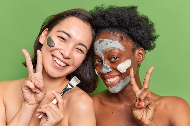 여성의 실내 사진은 완벽한 매끄러운 피부를 가진 평화 기호를 보여줍니다. 평화 기호는 녹색 벽에 격리된 얼굴에 영양 점토 마스크를 적용합니다