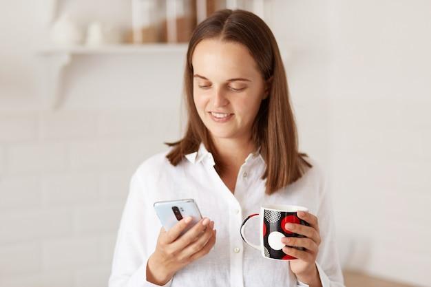 携帯電話を使用し、キッチンでコーヒーを飲み、手に飲み物を持って、デバイスのディスプレイを見ている若い大人の美しい女性の屋内ショット。